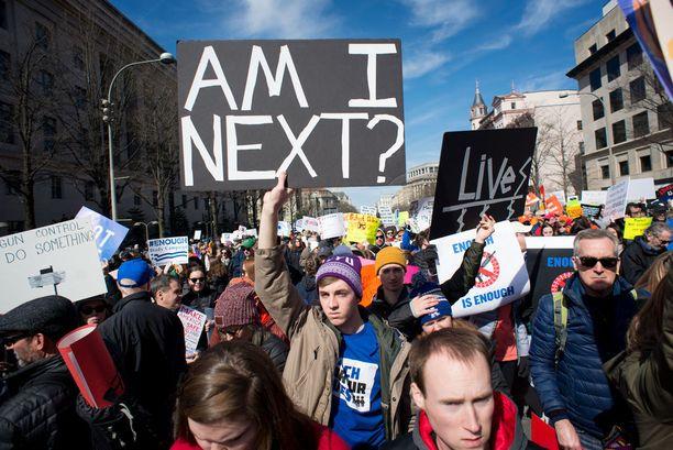 """Miljoonia ihmisiä kokoontui lauantaina sadoille eri paikkakunnille Yhdysvalloissa osoittamaan mieltä aseväkivaltaa vastaan. Kuva Washingtonista. Kyltissä lukee: """"Olenko minä seuraava?"""""""