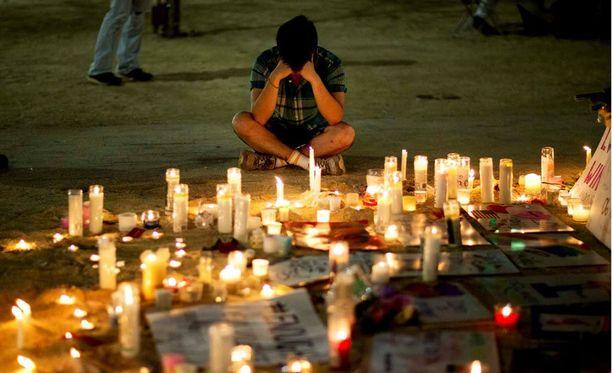 Ihmiset hiljentyvät ja surevat Pulse-yökerhon edessä joukkomurhan uhreja.