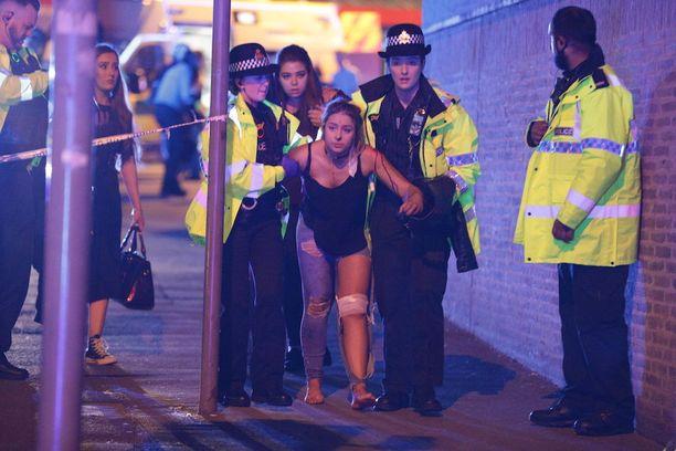 Silminnäkijöiden mukaan pommi räjähti Manchester Arenalla lähellä paikkaa, jossa myytiin Ariana Granden t-paitoja ja muita oheistuotteita. Kuvassa poliisiviranomaiset kannattelevat iskuissa loukkaantunutta nuorta.