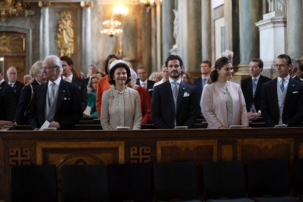 Kuningasperhe kirkon etupenkissä.