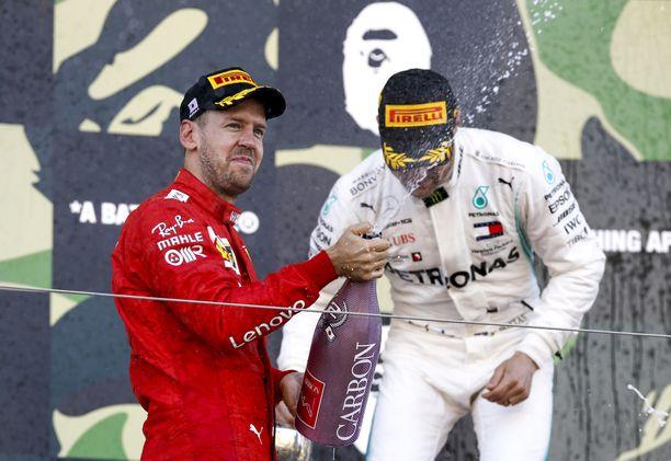 Sebastian Vettel juhli kakkossijaa Suzukan GP:n palkintopallilla kisan voittajan Valtteri Bottaksen kanssa.