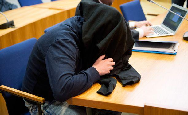 Syytetty peitto kasvonsa oikeudessa.