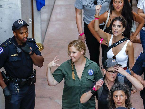 Amy Schumerin takana pidätettyjen joukossa valkoisessa topissa malli-näyttelijä Emily Ratajkowski.