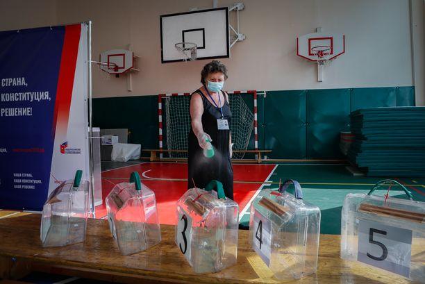 Paikallisen vaalikomitean jäsen desinfioi äänestyspaikkaa Moskovassa keskiviikkona.