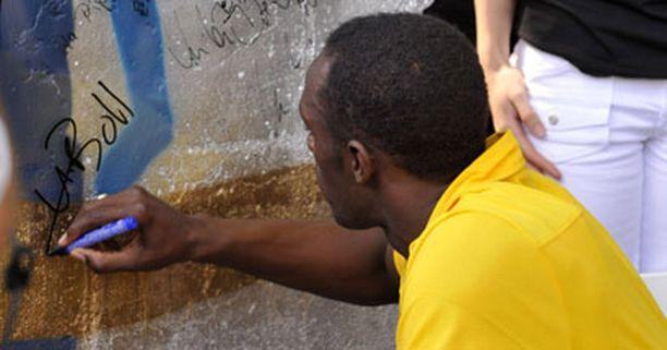 Usain Bolt kirjoitti nimikirjoituksensa muurinpalaan.