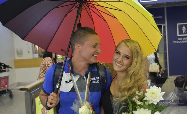 Pariskunta oli yhtä hymyä sateenkaaren värein koristellun sateenvarjon alla.