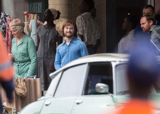 Daniel Radcliffe hymyili iloisesti kuvaajalle valmistautuessaan kohtaukseen.