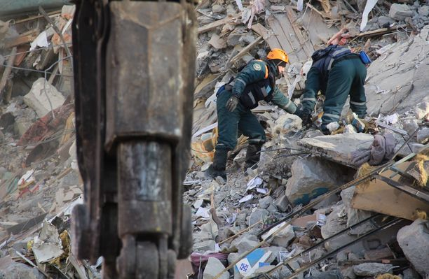 Pelastustyöntekijät etsivät onnettomuuden uhreja sortuneen talon raunioista Magnitogorskissa.