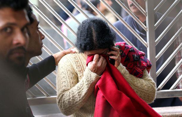 Nainen suri hotellipalossa kuollutta omaistaan ruumishuoneen edustalla Delhissä.