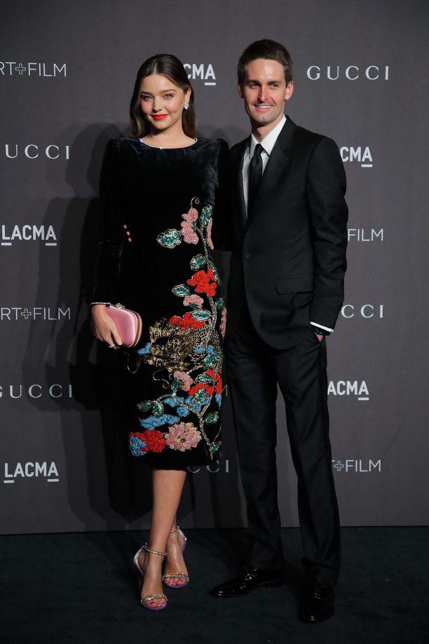 Miranda Kerr luottaa tyylissään nyt muodikkaaseen samettiin. Huomaa myös huulipuna, joka sointuu kauniisti mekon kirjailuihin! Vierellä Evan Spiegel.
