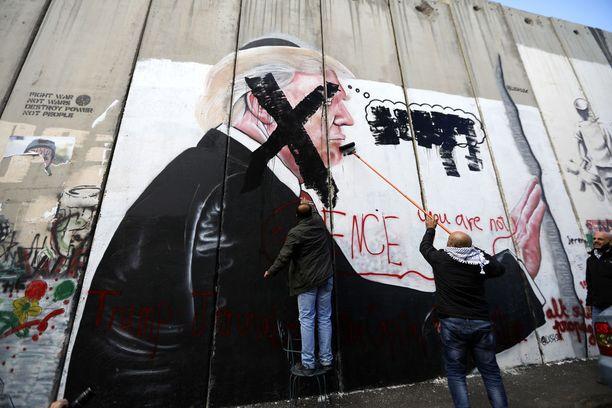Palestiinalaiset maalaavat suurta ruksia Yhdysvaltain presidentti Donald Trumpia esittävän seinämaalauksen päälle. Kuva on maalattu Isarelia ja miehitettyjä palestiinalaisalueita erottavaan muuriin.