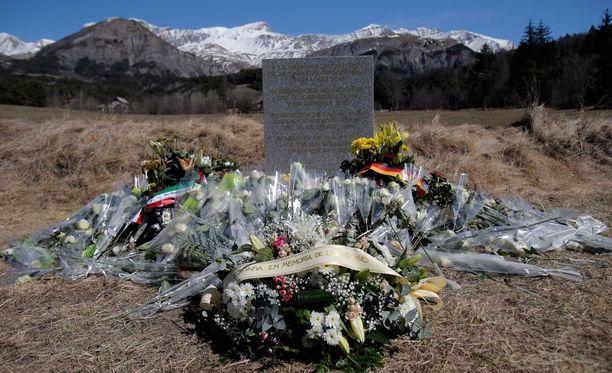 Turmapaikalle Alppien juurelle on tuotu muistolaatta ja kukkia.