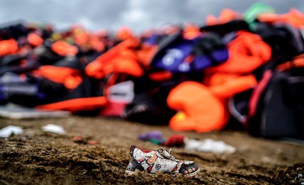 Rantaan hylättyjä ja huuhtoutuneita pelastusliivejä ja vaatteita kreikkalaisella Lesboksen saarella.