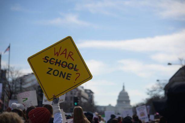 Koulualue vaihtui mielenosoittajan kyltissä sotatoimialueeksi. Kuva Washingtonista maaliskuun 24. päivältä.