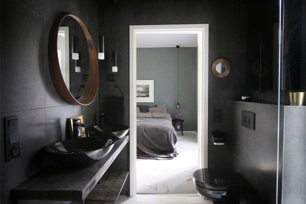Värimaailma muuttuu tummemmaksi kylpyhuoneessa ja makuuhuoneessa. Mustaan kylpyhuoneeseen on tuotu keveyttä pyöreiden yksityiskohtien avulla.