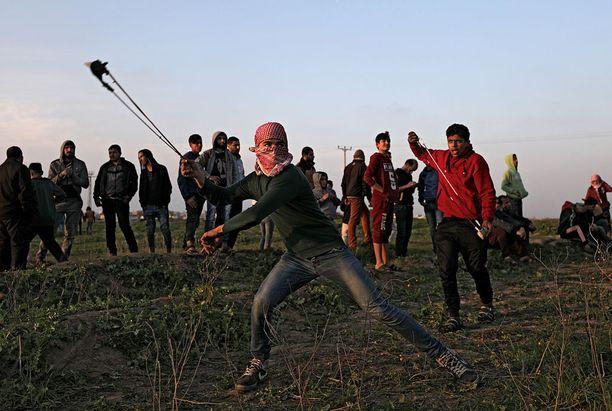 Palestiinalaiset mielenosoittajat heittivät kiviä Israelin joukkoja kohti perjantain mielenosoituksessa Gazan kaistaleella.