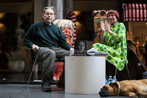 """Joulukuussa 86 vuotta täyttävän Pentti Linkolan esiintyminen Finlayson Art Areassa järjestyi Rosa Liksomin ansiosta. Liksom esitteli vieraansa """"Suomen tunnetuimpana luonnonsuojelijana ja monien mielestä Suomen ainoana intellektuellina"""". Linkolan mielestä luonnehdinta oli liioiteltu. Etualalla FAA-koira Pelle."""