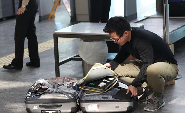 Matkustaja avaa laukkunsa ja näyttää läppäriä turvatarkastuksessa Turkin Istanbulissa.