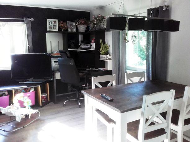 Takan ja sohvan lisäksi olohuoneessa on ruokapöytä, tietokonetaso ja televisio,