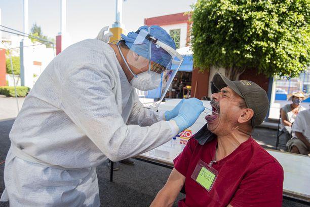 Terveystyöntekijät tekevät koronatestejä pakolaisille Meksikossa toukokuussa.