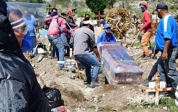 Työntekijät laskevat desinfioidun arkun hautaan San Isidrossa, Ecatepecin kunnassa.