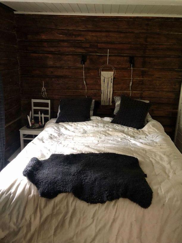 Makuuhuoneessa tummaan hirsipintaan on yhdistetty valkoista.