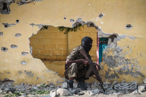Somalian turvallisuusjoukkojen jäsen istui vartiossa lähellä maan tiedusteluvirastoa, jonnea terroristijärjestö al-Shabaab oli iskenyt. Kuva Mogadishusta viime kesältä.