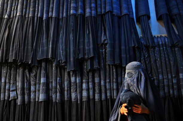 Nainen ostamassa burkhaa kaupasta Mazar-i-Sharifissa. Kuvituskuva vuodelta 2015.