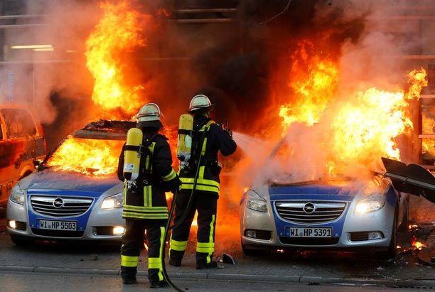 Palomiehet sammuttivat liekehtiviä poliisiautoja aamulla Frankfurtissa.