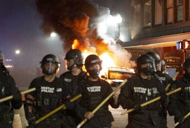 Mielenosoituksissa ympäri USA:ta on ollut väkivaltaa, mutta vielä ei tiedetä tarkkaan, ketkä väkivaltaisuuksien takana ovat. Poliisi seisoi palavan talon edessä Bostonin kaupungissa Massachusettsissa sunnuntaina.