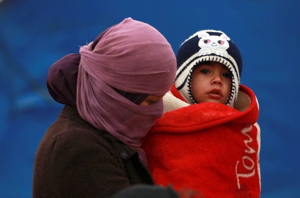 Irakilaisnainen piti tänään lasta sylissään hyytävässä kylmyydessä pakolaisleirillä Khazirissa Mosulin lähellä.