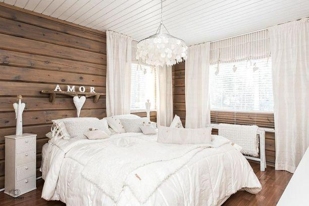 Makuuhuoneeseen on saatu unenomainen tunnelma hyödyntämällä ainoastaan valkoista väriä. Asetelma toimii, koska lattia ja seinät ovat tummat. Kappaverhojen ja sivuverhojen yhdistelmä lisää romanttista tunnelmaa.