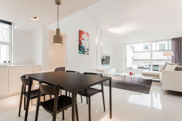 Kodin valkoisia pintoja on maustettu mustalla ruokailuryhmällä ja harmahtavilla tekstiileillä.