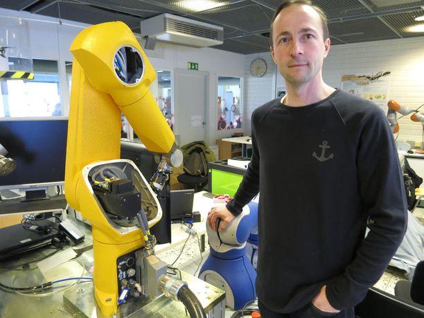 Suomen Robotiikkayhdistyksen puheenjohtaja Jyrki Latokartano esittelee Tampereen teknillisen yliopiston robotiikkalaboratorion hienouksia.