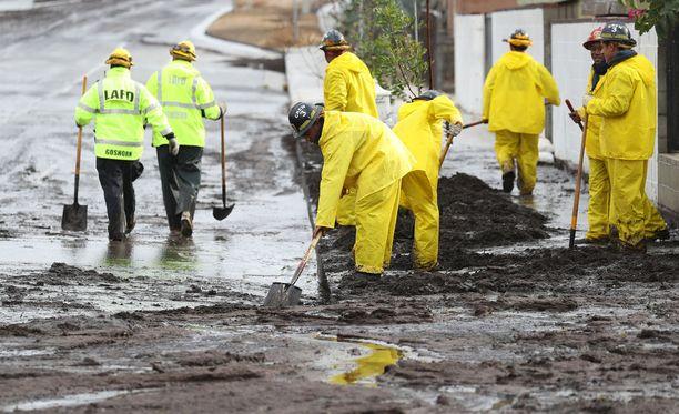 Los Angelesin palokunnan pelastustyöntekijät tekevät työtä tulvaveden ja mudan keskellä.