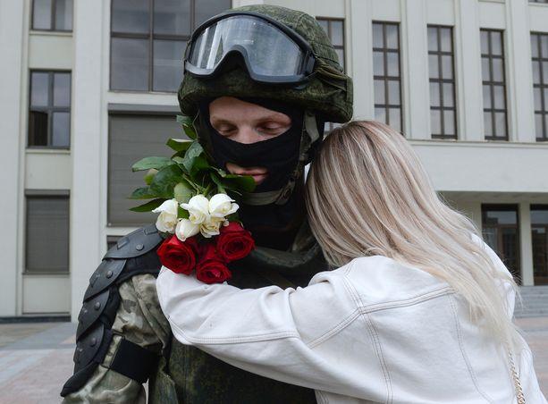 Nainen halasi turvallisuusjoukon jäsentä mielenosoituksen aikana perjantaina.