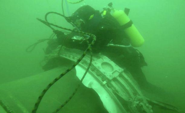 Sukeltajat tutkivat koneen jäännöksiä.