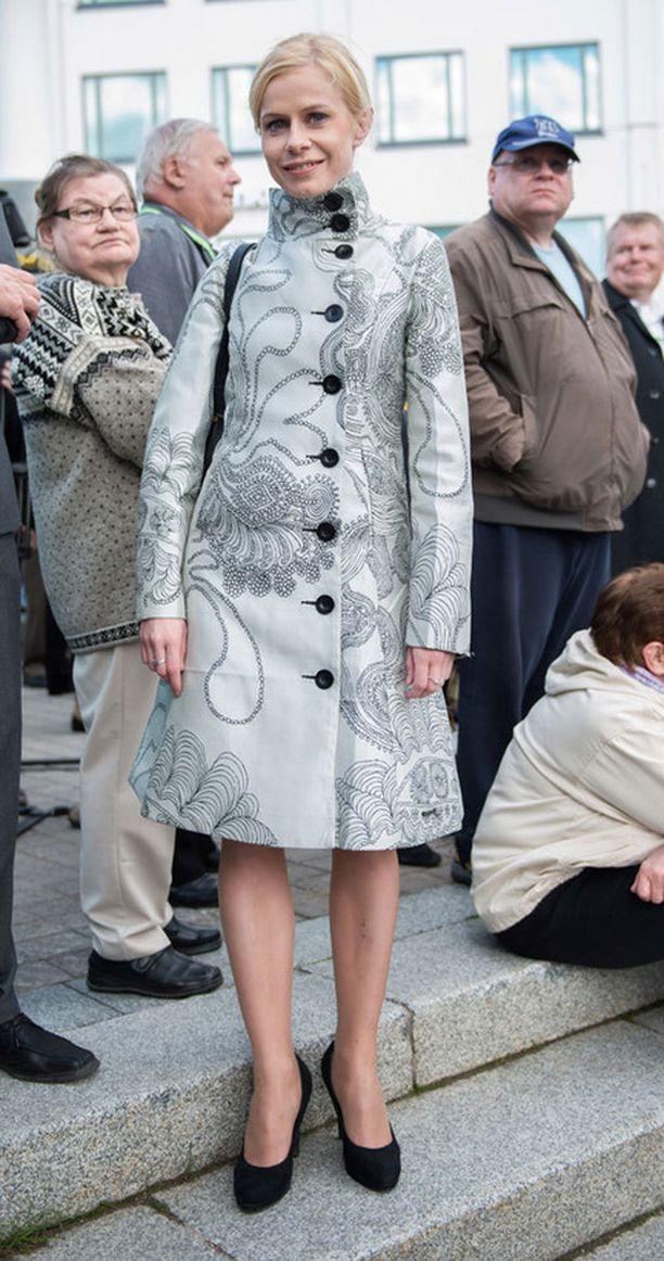Riikka Manner pukeutui puoluekokouksen yleisötapahtumaan harmaaseen kevättakkiin.