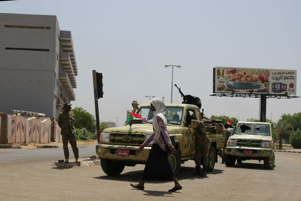 Nainen käveli nopean toiminnan joukkojen auton ohi Sudanissa lähellä mielenosoitusta, jonka armeija hajotti verisesti. EPA
