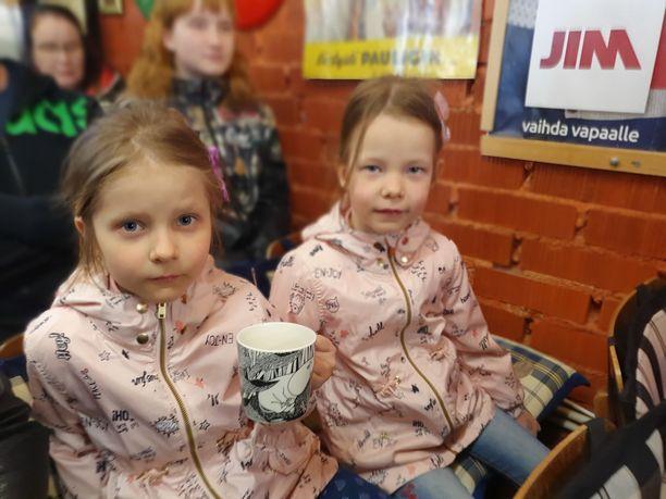 Kuvassa muumimukin ostaneen perheen kaksoset Ella ja Emma.