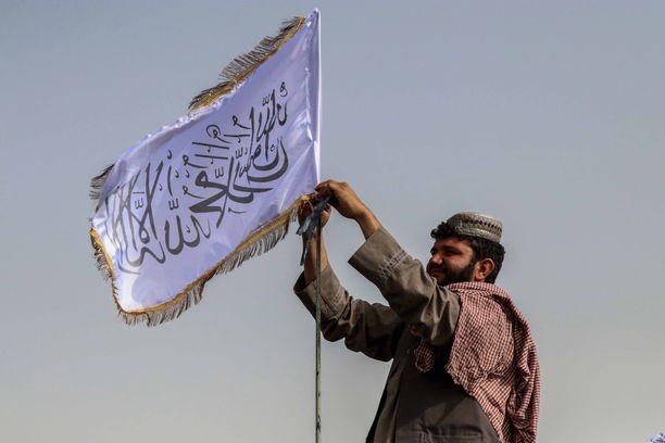 Talibanin taistelija nostamassa lippua partioauton salkoon. Taliban julisti maanantaina vallanneensa maan ja voittaneensa sodan.