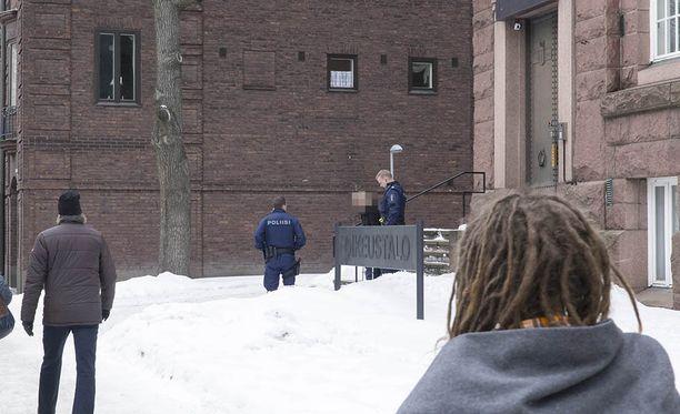 Poliisit saattoivat naisen käräjäoikeudesta partioautoon.