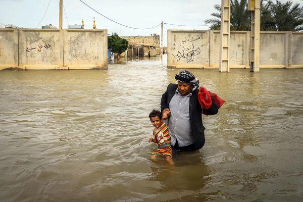 Iranilainen mies kantaa poikaansa tulvivassa kylässä lähellä Ahvazia.