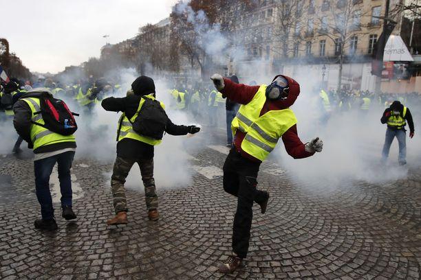 Mielenosoittajat heittivät kyynelkaasupatruunoita takaisin poliiseja kohti.