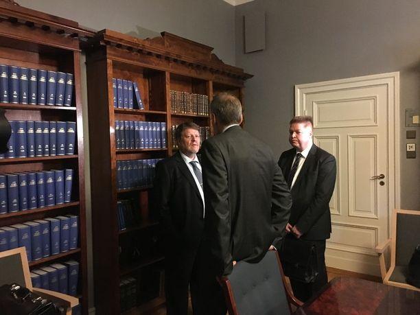 Apulaisoikeuskansleri Kimmo Hakonen, asianajaja Jarkko Jaatinen (selin kameraan) ja oikeuskanslerinviraston kansliapäällikkö Petri Martikainen keskustelivat ennen valmisteluistunnon alkamista.