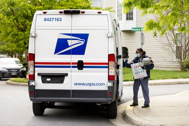 Yhdysvaltain postilaitos USPS:n postinkantaja kuljetti huhtikuussa 2020 posteja kasvomaskiin sonnustautuneena.