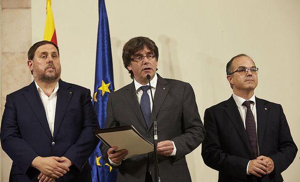 Katalonian aluehallinnon johtaja Carles Puigdemont (keskellä) on allekirjoittanut asetuksen alueen itsenäisyyttä koskevan kansanäänestyksen järjestämisestä
