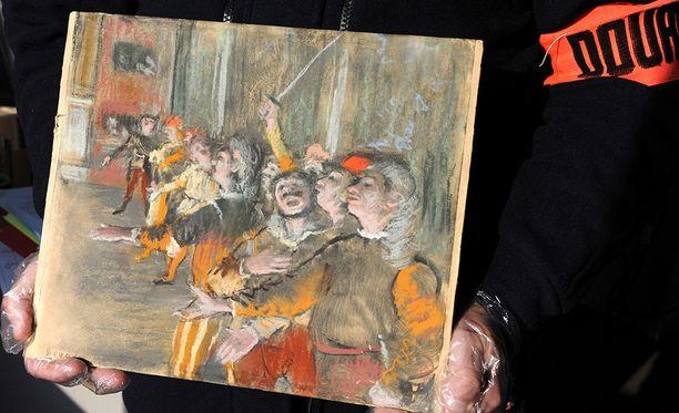 Ranskalainen tullivirkailija esittelee linja-autosta löytynyttä Les Choristes -maalausta.