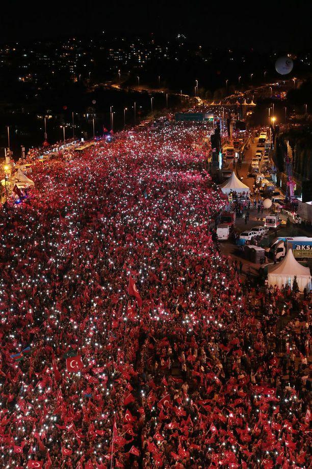 Valo vilkkui matkapuhelinten näytöiltä väenpaljoudessa Istanbulissa.