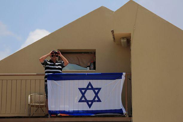 Israelilaismies kiikaroi Gazan pommitusta kotiparvekkeeltaan.